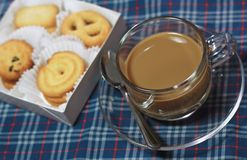 Cup of coffee and cookies on chintz Scots. Stock Photo