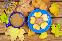 Cup of coffee and cookies with dried autumn leaves. Stock Image