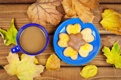Cup of coffee and cookies with dried autumn leaves. Royalty Free Stock Photos