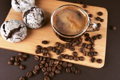 Cup of coffee with cookies. Cup of coffee with foam, with cookies and coffee beans, lying on the wooden stand, on brown background Royalty Free Stock Photography