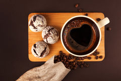 Cup of coffee with cookies. Cup of coffee with foam, with cookies and coffee beans, lying on the wooden stand, on brown background Royalty Free Stock Images
