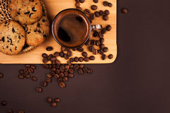 Cup of coffee with cookies. Cup of coffee with foam, with cookies and coffee beans, lying on the wooden stand, on brown background Stock Photo