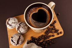 Cup of coffee with cookies. Cup of coffee with foam, heart shaped, with cookies and coffee beans, lying on the wooden stand, on brown background Royalty Free Stock Photography