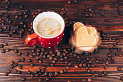 Cup of coffee with cookies. Cup of coffee with foam, heart shaped cookies and coffee beans, lying on the wooden stand, on wooden table Royalty Free Stock Photo