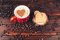 Cup of coffee with cookies. Cup of coffee with foam, heart shaped, with heart shaped cookies and coffee beans, lying on the wooden stand, on wooden table Stock Photography