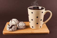 Cup of coffee with cookies. Cup of coffee with foam, with cookies, lying on the wooden stand, on brown background Royalty Free Stock Photo