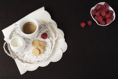 Cup of coffee, cookies a jug of milk on a straw tray. A bowl with raspberries. Black background. Top view. Cup of coffee, cookies a jug of milk on a straw tray Stock Image