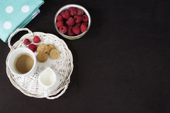 Cup of coffee, cookies a jug of milk on a straw tray. A bowl with raspberries. Black background. Top view. Cup of coffee, cookies a jug of milk on a straw tray Royalty Free Stock Photo
