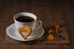 A cup of coffee and cookies like heart, cinnamon, coffee beans on wooden table on dark background Stock Photo