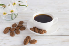 Cup of coffee, cookies and narcissus on white wooden background royalty free stock photos