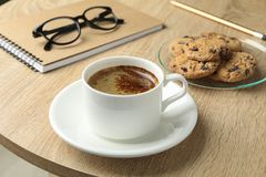 Cup of coffee, cookies, notebook and glasses on wooden table, closeup and space for text stock image