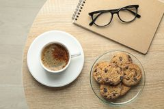 Cup of coffee, cookies, notebook and glasses on wooden table, top view and space for text stock photo