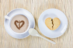 Cup of coffee and cookies in the shape of a broken heart Royalty Free Stock Photography