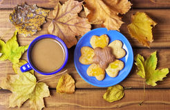 Cup of coffee and cookies on the table with autumn leaves. Stock Photos