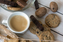 Cup of coffee, cookies, walnut and chocolate on white wooden background Royalty Free Stock Image