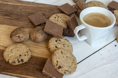 Cup of coffee, cookies, walnut and chocolate on white wooden background Royalty Free Stock Photo