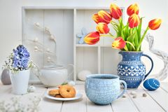 Coffee and cookies on white table with red tulips and springtime Royalty Free Stock Image