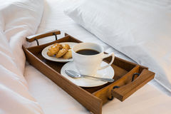 Cup of coffee and cookies in wooden tray on comfortable bed Royalty Free Stock Photography