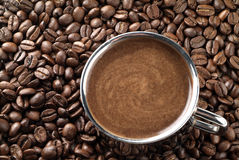 Cup with coffee, costing on coffee grain. Royalty Free Stock Photo