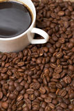 Cup with coffee, costing on grain. Cup with coffee, costing on coffee grain Royalty Free Stock Photo
