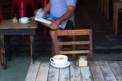 The cup of coffee costing on a wooden little table, a cappuccino, coffee with milk, fragrant a cappuccino. Stock Photo