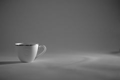 A Cup of coffee costs in a beam of light, monochrome Royalty Free Stock Photos
