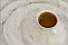 Cup with coffee costs on sand Royalty Free Stock Photography