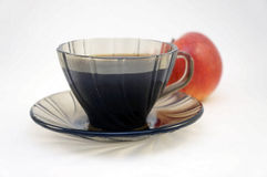 Morning coffee. The cup with coffee costs on a saucer, behind there is an apple Royalty Free Stock Images