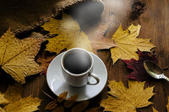 Cup of coffee costs on a wooden table. Surrounded by autumn leaves Stock Photo