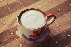 A cup of coffee on cotton fabrics background, process in vintage Royalty Free Stock Photo
