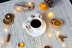 A cup of coffee with cotton and oranges on a wooden background. stock image