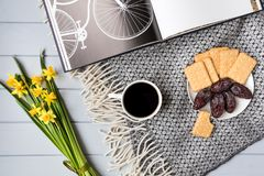 Cup of coffee, cracker biscuit cookies, date fruits, book with bicycle and daffodil flowers. Top view, flat lay Royalty Free Stock Photos