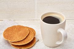 Cup of coffee and biscuit  on the white background, close-up, shallow depth of field. Cup of coffee with cream and biscuit  on the white background. Concept Royalty Free Stock Photos