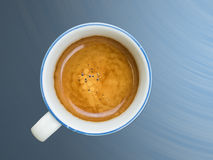 Cup of coffee with cream. Cup of coffee on blue background Royalty Free Stock Photography