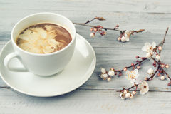 Cup of coffee with cream and cherry tree flowers on grey wooden background, vintage filter Royalty Free Stock Image