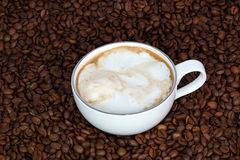 Cup of coffee with cream on a coffee beans background Royalty Free Stock Image