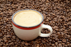Cup of coffee with cream on a coffee beans background Stock Photos