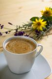 Cup of coffee with cream in front of flowers Stock Photo