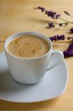 Cup of coffee with cream on light table Royalty Free Stock Images