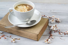 Cup of coffee with cream on the old book, wooden background with blooming cherry branches Royalty Free Stock Photography