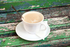 Cup of coffee with cream is on old wooden bench Stock Photos