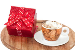 A cup of coffee with cream and red gift box with bow Royalty Free Stock Photo