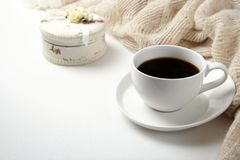 A Cup of fragrant black coffee and a textured wool blanket. Warm tone royalty free stock photo