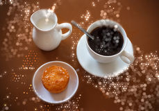 Cup of coffee, creamer jug and muffin on reflective table Royalty Free Stock Image