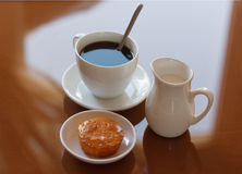 Cup of coffee, creamer jug and muffin on reflective table Royalty Free Stock Images