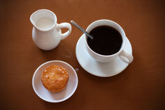 Cup of coffee, creamer jug and muffin on reflective table Stock Photography