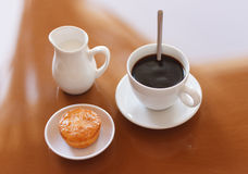 Cup of coffee, creamer jug and muffin on reflective table Stock Images