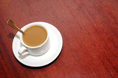A cup of coffee with creamer. On the table Royalty Free Stock Photo