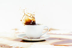 Cup of coffee creating splash. White background, coffee stains. Stock Photography