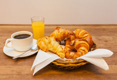 Cup of coffee with croissant in a basket orange juice Royalty Free Stock Image